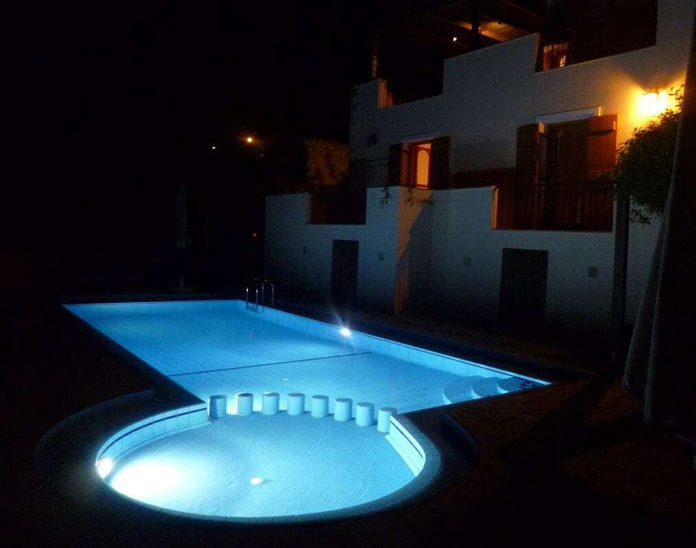 The pool is illuminated in the evening.
